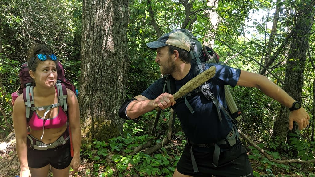 Guy beating woman on a hiking trail joke photo