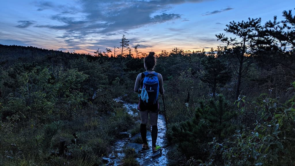 girl with bun and blue backpack walking on a wet mountain trail at sunrise, the water on the trail is reflecting the sunrise