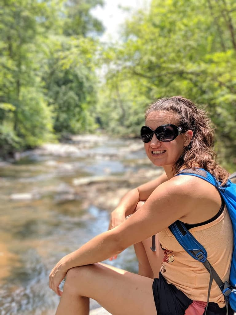 Girl with sunglasses and orange shirt wearing a backpack and sitting in front of a creek smiling