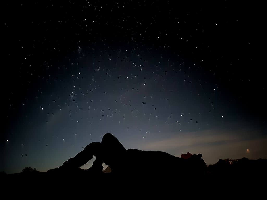 A silhouette of a girl lying on her back and looking at the stars